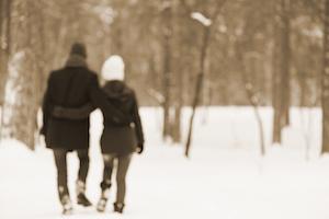 couple walks through forrest in winter