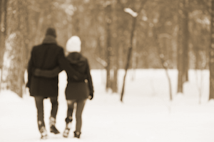 couple walks through forrest in winter